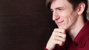 一个红色衬衣手指的年轻人在他的嘴唇,仔细地看 影视素材