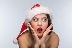 一个红色裙子和圣诞老人帽子的少妇在一轻的backgr 库存照片
