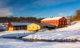 一个红色谷仓和一条小河在七个谷, Pennsyl的冬天视图 库存照片