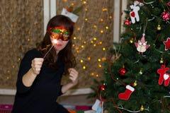 一个红色面具的女孩在与闪烁发光物的一棵圣诞树附近 库存照片