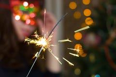 一个红色面具的女孩在与闪烁发光物的一棵圣诞树附近 免版税库存图片