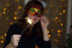 一个红色面具的女孩在与闪烁发光物的一棵圣诞树附近 免版税库存照片