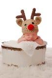 戴一个红被引导的驯鹿帽子的微笑的婴孩 免版税库存图片