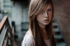一个红头发人女孩的特写镜头画象有站立在台阶和看照相机的雀斑和蓝眼睛的 免版税库存图片