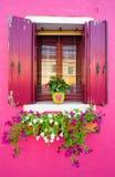 一个绯红色房子的视窗 库存照片