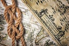 一个绳索海结的特写镜头视图在一张老减速火箭的地图的 免版税库存照片