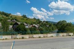 一个绿色山坡的村庄在一座桥梁的一条柏油路后横跨一条风雨如磐的河在蓝色多云天空下 库存照片