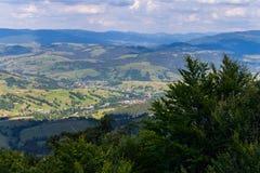 一个绿色山谷的全景与村庄的反对多云多云天空背景 免版税图库摄影