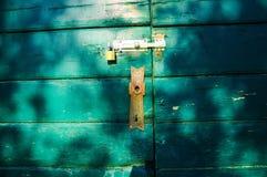 一个绿色木门的生锈的锁 库存图片
