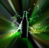 一个绿色瓶与浓缩的水下落的啤酒它的表面上和液体飞溅由辐形五颜六色的光线点燃了 免版税库存照片