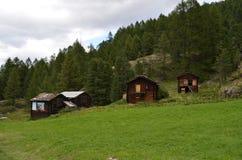 一个绿色草甸的古老木民间山房子在策马特附近,瑞士高山村庄  库存照片