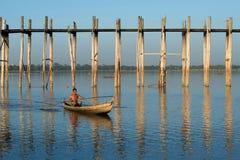 一个缅甸人在一条传统木小船游泳在Thaungthaman湖的老U Bein桥梁 图库摄影