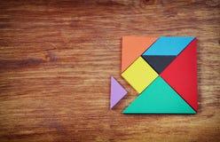 一个缺掉片断的顶视图在一个方形的七巧板难题的,在木桌 库存照片