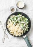 一个罐乳脂状的鸡菠菜和绿豆farfalle面团在平底锅在白色背景,顶视图 免版税库存图片