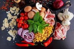 一个罐平底锅面团用烟肉,栗子采蘑菇,西红柿、红洋葱、conchiglie和蓬蒿叶子 免版税库存图片