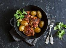 一个罐烘烤了harissa鸡和嫩土豆土豆在黑暗的背景 免版税图库摄影