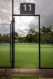 一个网球场的看法通过在篱芭的开放门对法院 库存图片