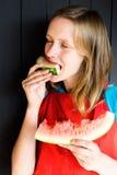 一个美丽和女孩咬住一个新鲜,可口和水多的西瓜 她非常饿并且要吃它 库存照片