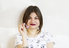 一个美丽和微笑的女孩拿着一个棒棒糖 库存照片
