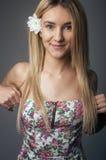 一个美丽和柔和的白肤金发的女孩的画象在蓝色背景的演播室在礼服 免版税库存照片