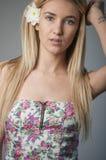 一个美丽和柔和的白肤金发的女孩的画象在蓝色背景的演播室在礼服 免版税图库摄影