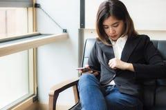 一个美丽的亚裔女商人坐拿着巧妙的电话和检查她的衣服的沙发今天见面 图库摄影