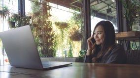 一个美丽的亚裔女商人的特写镜头图象举行和谈话在有膝上型计算机的巧妙的电话在木桌上 库存图片