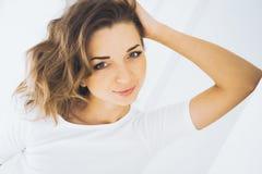 一个美丽的亭亭玉立的性感的逗人喜爱的女孩的画象在一张床上的与在白色顶面白肤金发的白色亚麻布醒并且舒展并且微笑 免版税库存照片