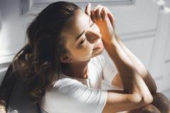 一个美丽的亭亭玉立的性感的逗人喜爱的女孩的画象在一张床上的与在白色顶面白肤金发的白色亚麻布醒并且舒展并且微笑 库存图片