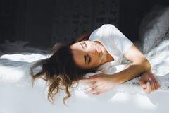 一个美丽的亭亭玉立的性感的逗人喜爱的女孩的画象在一张床上的与在白色顶面白肤金发的白色亚麻布醒并且舒展并且微笑 库存照片