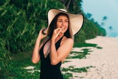 一个美丽的光亮的女孩在度假基于海滩的,诱人地接触她的嘴唇,快乐地微笑,佩带 免版税库存照片