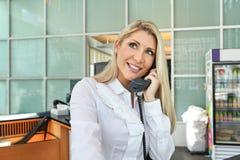 一个美丽的办公室夫人谈话在有微笑的电话 库存图片