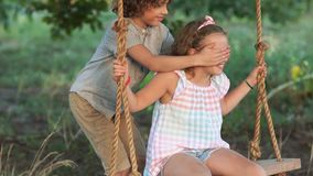 一个美丽的卷曲女孩在摇摆乘坐 男孩方法从后面闭上她的眼睛 儿童游戏,夏天 股票录像