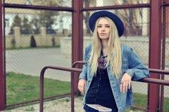 一个美丽的哀伤的白肤金发的女孩的画象户外在帽子 免版税库存图片