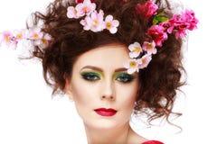 一个美丽的在头发的春天女孩佩带的花的画象 stu 免版税库存图片