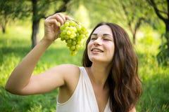 一个美丽的女孩享受葡萄芳香紧密  免版税库存图片