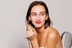 一个美丽的女孩光秃的肩膀在她的手上坐椅子并且拿着一只鬣鳞蜥壁虎并且按她对她的面孔 免版税库存照片
