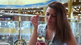 一个美丽的女孩吃一个甜蛋糕,当坐在咖啡馆时的一张桌上 股票视频