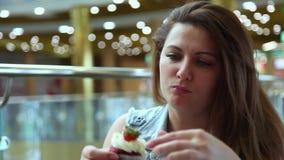 一个美丽的女孩吃坐在有的咖啡馆的一张桌上的一个甜蛋糕一种好心情 股票视频