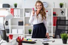一个美丽的女孩在一张桌附近在她的手上站立在办公室并且拿着一个桃红色标志 在女孩前有 库存图片