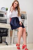 一个美丽的女孩在一张桌附近在她的手上站立在办公室并且拿着一支红色铅笔 免版税库存图片