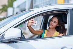 一个美丽的女孩在一辆新的汽车被拍摄 选择一辆新的汽车 库存照片