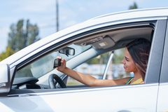 一个美丽的女孩在一辆新的汽车被拍摄 选择一辆新的汽车 库存图片