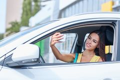 一个美丽的女孩在一辆新的汽车被拍摄 选择一辆新的汽车 免版税库存照片