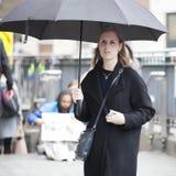 一个美丽的女孩在伞下走伦敦街道  库存图片