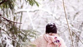 一个美丽的女孩在冬天森林在雪高兴 她在一件桃红色外套、手套和黑帽会议打扮 股票录像