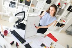 一个美丽的女孩在办公室在桌附近在一个磁性黑板站立并且解释石渣 库存图片