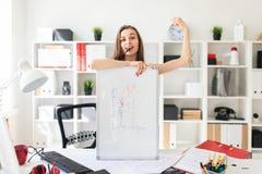 一个美丽的女孩在办公室在桌附近站立,把放她的手在磁性板,举行上一个桃红色标志 免版税库存照片