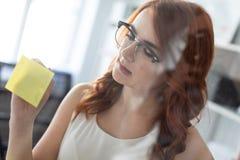 一个美丽的女孩在办公室站立在贴纸被黏贴的玻璃附近 女孩拿着一支铅笔  库存图片