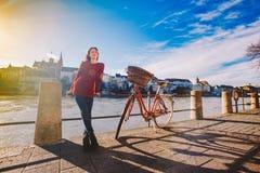 一个美丽的女孩在堤防在有红色篮子的一辆城市自行车附近在瑞士,市站立巴塞尔 晴朗 库存照片